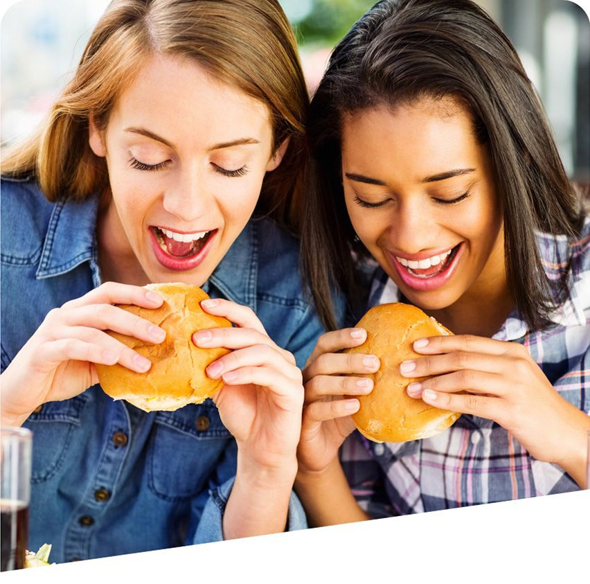 Two young women enjoying sandwiches made with freshly baked bread.